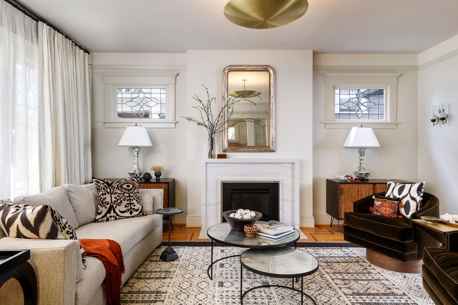 Holland Stephens Interiors - View south into the living room with new custom marble fireplace and vintage mirror. Touch of modern with a brass, disc chandelier.