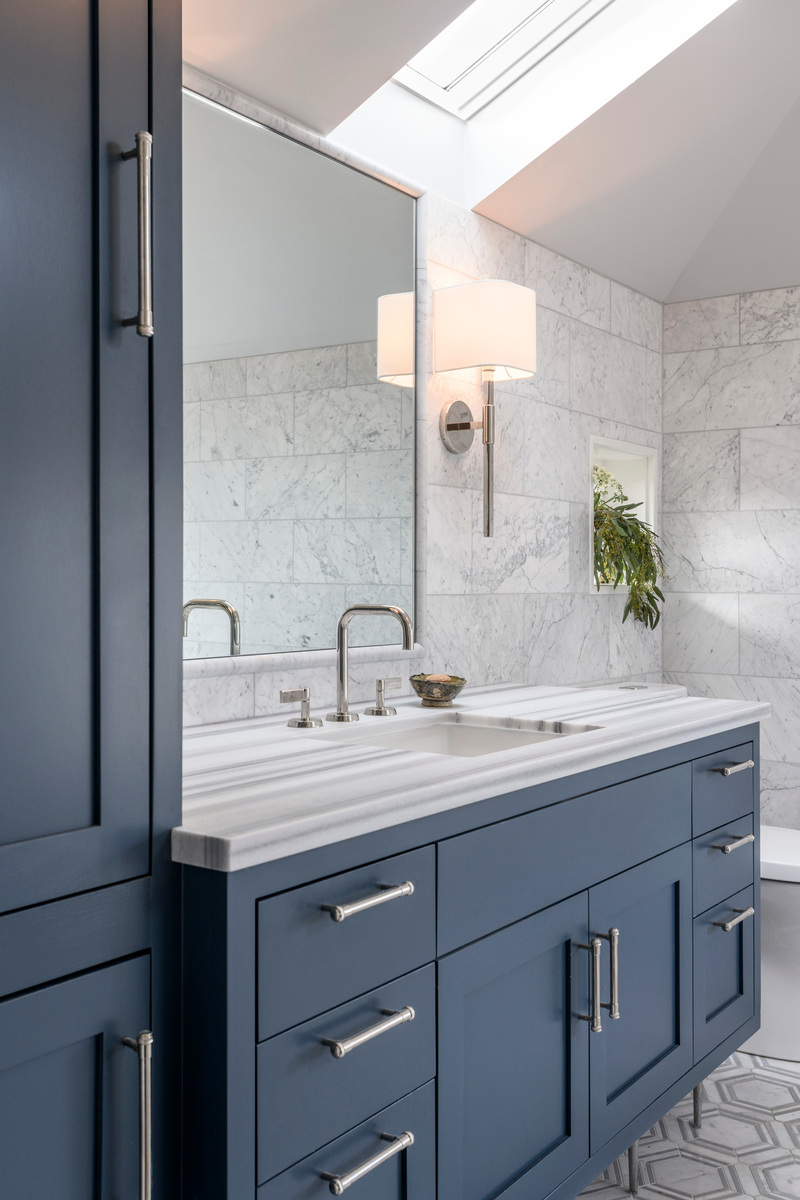 Holland Stephens Interiors - Remodeled masterbath with crisp tailored blue cabinetry and marble hex flooring.